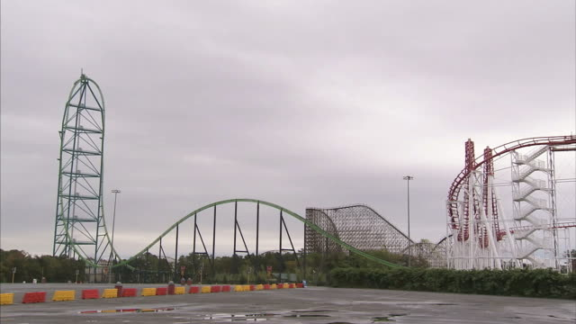 wide shot static - storm clouds loom above a roller coaster / six flags great adventure jackson, nj - jackson new jersey stock videos and b-roll footage