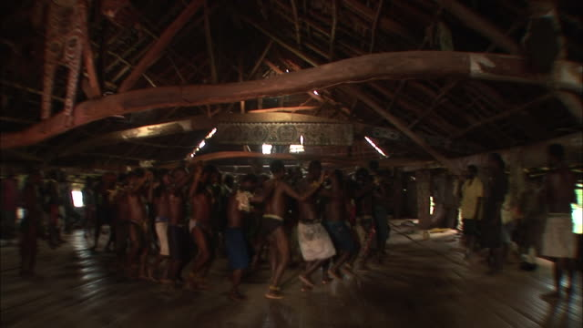 Wide Shot static - Villagers dance in a spirit house. / Papua New Guinea