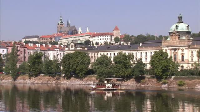 Wide Shot static-Domed buildings overlook a ferry on a river. / Prague, Czech Republic
