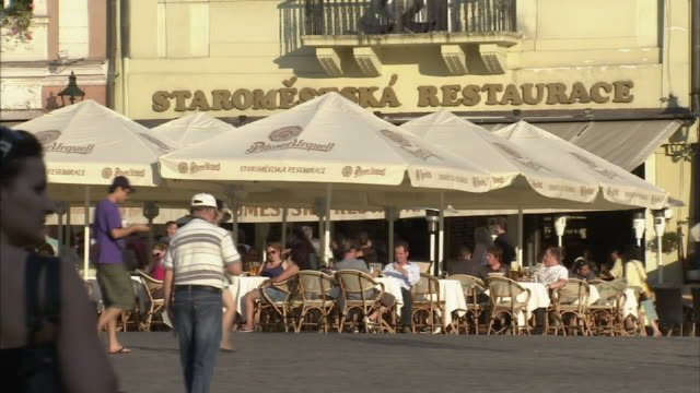 wide shot static-pedestrians pass an outdoor cafe in a town square. / prague, czech republic - prague old town square stock videos & royalty-free footage