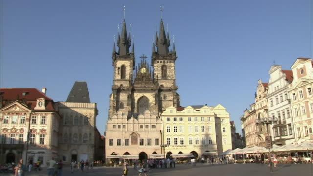 Wide Shot static-Pedestrians pass through a beautiful town square in Prague. / Prague, Czech Republic