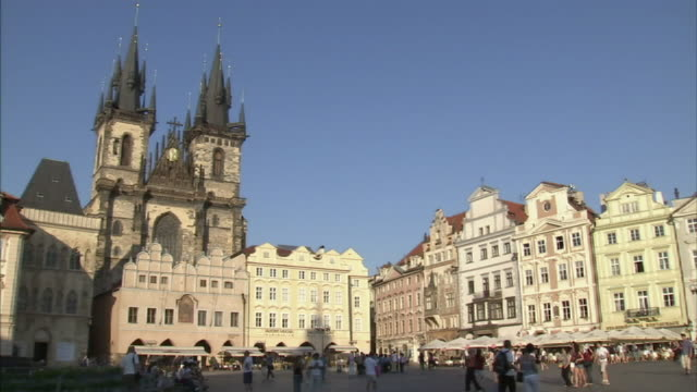 Wide Shot static-Pedestrians walk through a town square in Prague. / Prague, Czech Republic