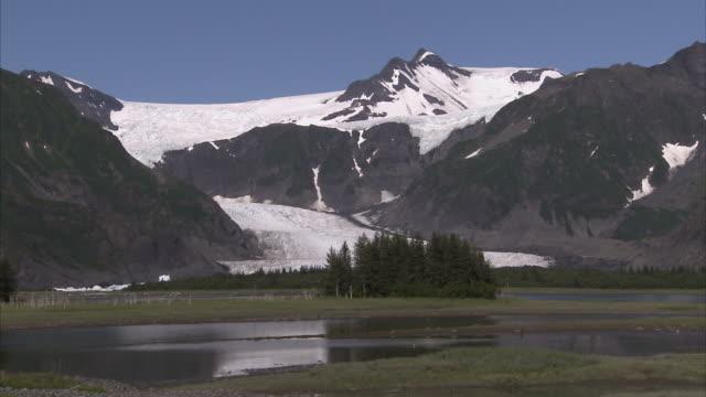 """wide shot static-snow covered mountains rise above a lake in alaska. / kenai peninsula, alaska, usa"" - kenai peninsula stock videos & royalty-free footage"