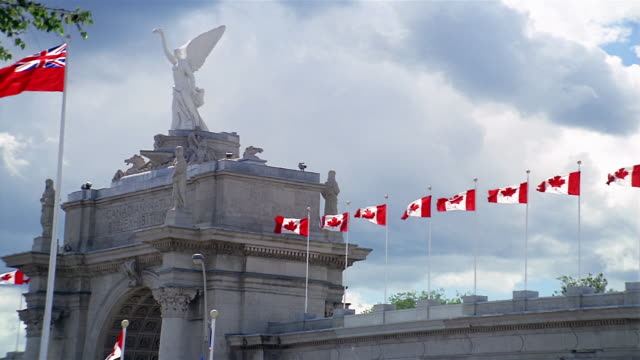 wide shot statue and canadian flags on princes' gate at exhibition place / heavy clouds in sky / toronto - kelly mason videos 個影片檔及 b 捲影像