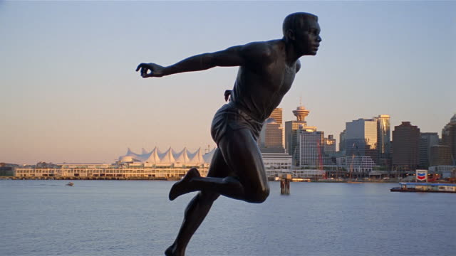 wide shot statue of harry jerome crossing finish line with view of harbor and skyline / vancouver - kelly mason videos stock videos & royalty-free footage