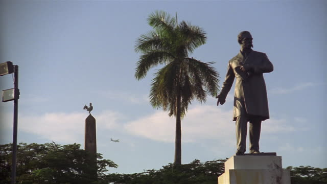 wide shot statue of pablo arosemena in park with plane flying by/ panama city, panama - mittelamerika stock-videos und b-roll-filmmaterial