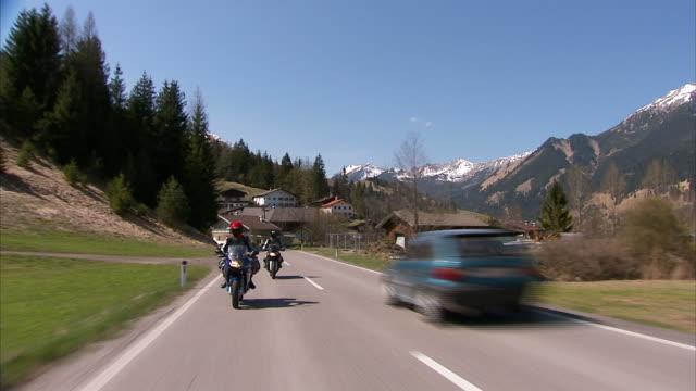 wide shot steadicam - motorcyclists ride on a scenic mountain road. / germany - 乗物後部から見た視点点の映像素材/bロール