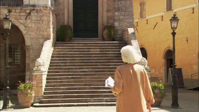 vídeos de stock, filmes e b-roll de wide shot steps and doorway to old building/ zoom in medium shot mature woman walking in with guidebook and looking around/ woman looking at book, looking around, and walking off camera/ norcia, umbria - old book