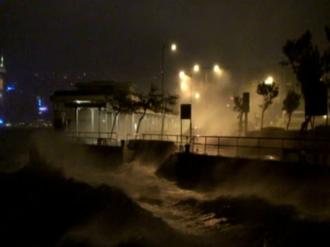 Wide shot storm waves lashing sea wall, Typhoon Koppu, Hong Kong on night of 14th sept 2009. With Audio.