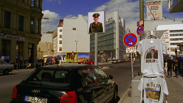 wide shot street + large poster of russian soldier at checkpoint charlie / t-shirt stand in foreground / berlin - poster stock-videos und b-roll-filmmaterial