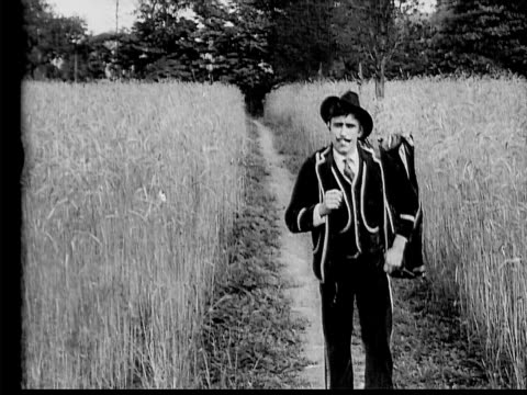 stockvideo's en b-roll-footage met 1910 b/w wide shot suave smoking man with moustache in suit walking down path in wheat field  - 1900 1909