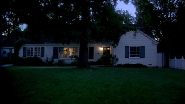 Wide shot suburban house and yard at night
