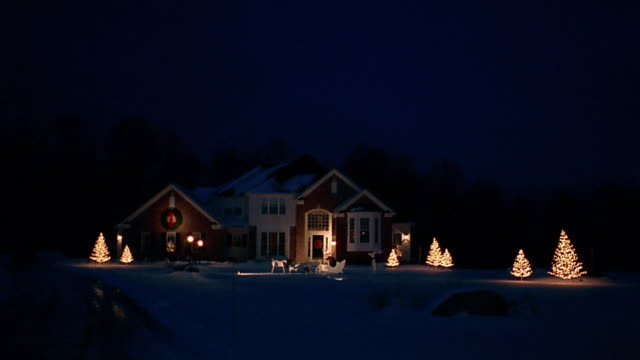 Wide shot suburban house with Christmas lights at night