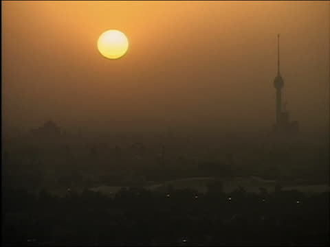 vidéos et rushes de 2003 wide shot sun setting and helicopters in silhouette flying over sunset / baghdad iraq - 2003