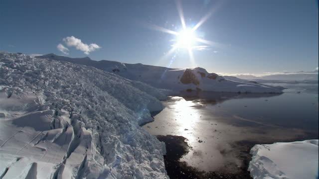 wide shot sunbeams shining over glaciers along coast of antarctic sea/ antarctica - crevasse stock videos & royalty-free footage