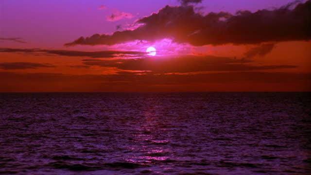 wide shot sunset behind clouds over ocean - meerlandschaft stock-videos und b-roll-filmmaterial
