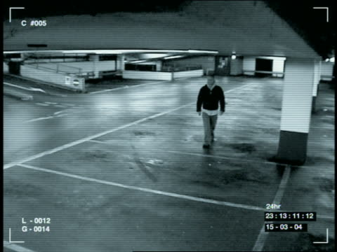 wide shot surveillance cam man stealing car in parking garage - sorveglianza video stock e b–roll