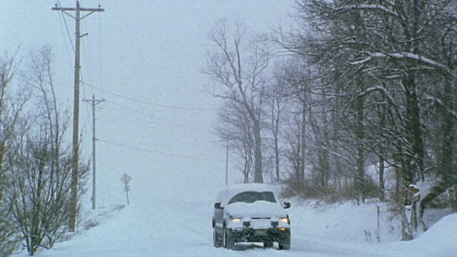 wide shot suv driving on country road in snow storm - pennsylvania stock videos and b-roll footage