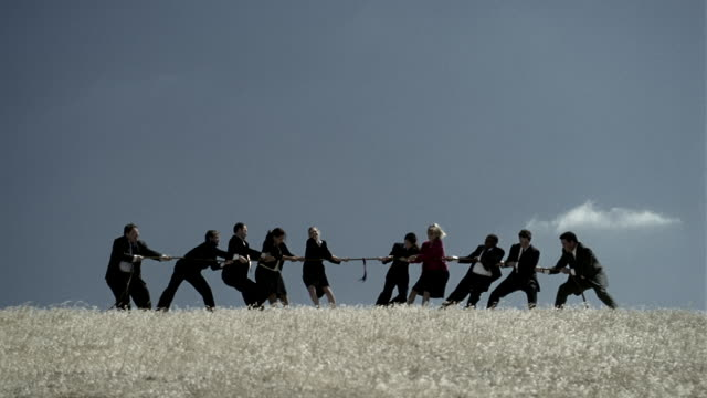 Wide shot swish pan zoom in businesspeople playing tug of war in field