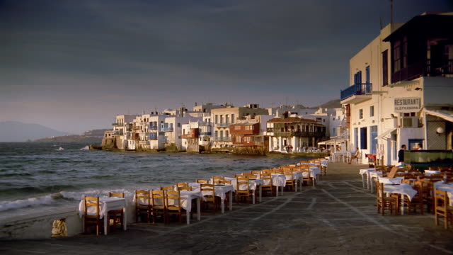 wide shot tablecloths on tables flapping in the wind at outdoor cafe with water in background / mykonos, greece - mykonos stock videos and b-roll footage