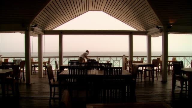 vídeos y material grabado en eventos de stock de wide shot tables on covered deck at vacation resort/ hotel worker entering and straightening up/ harbour island, bahamas - hospitalidad