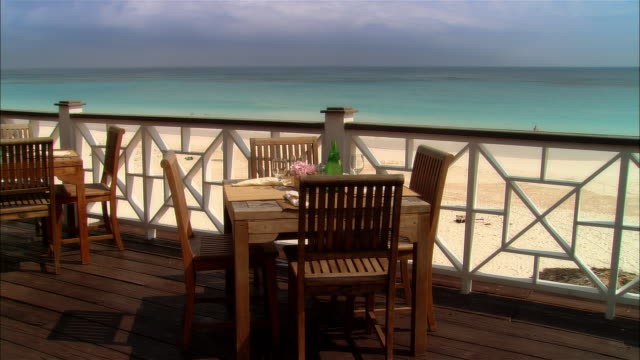 Wide shot tables on deck at vacation resort overlooking beach/ Harbour Island, Bahamas