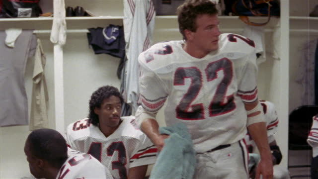 1985 Wide shot Tampa Bay Bandits player Joel Blunk talking to teammate and walking in locker room before game / USA