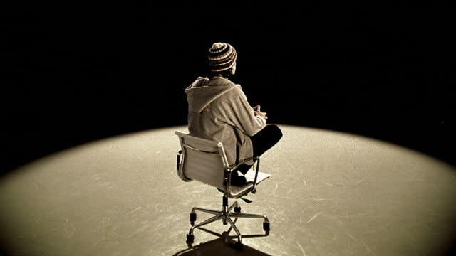 wide shot teenage boy wearing sweatshirt and cap kneeling in office chair as it spins under spotlight - 18 19 years stock videos & royalty-free footage