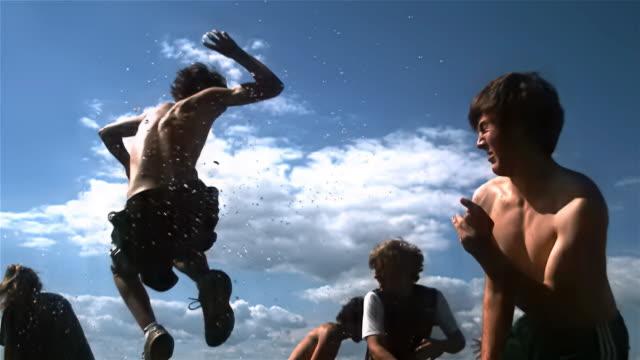 vídeos de stock e filmes b-roll de wide shot teenage boys and young man jumping and throwing water balloons/ mystic, connecticut, usa - bomba de água equipamento