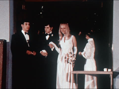 1970 wide shot teenage couples in formal dress arriving at prom / boy in tuxedo announcing names - 高校卒業ダンスパーティ点の映像素材/bロール