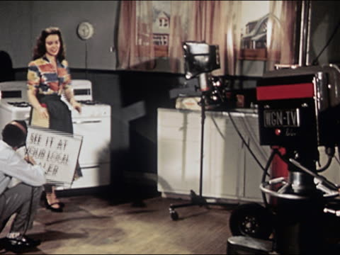 1953 wide shot television commercial being shot in studio with woman holding up sign / audio - advertisement stock videos & royalty-free footage