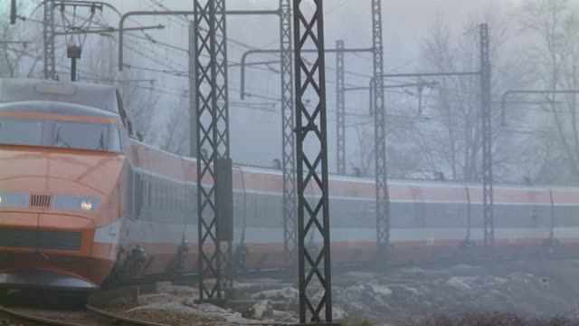 Wide shot TGV train rounding track toward CAM on foggy day / passing CAM / France