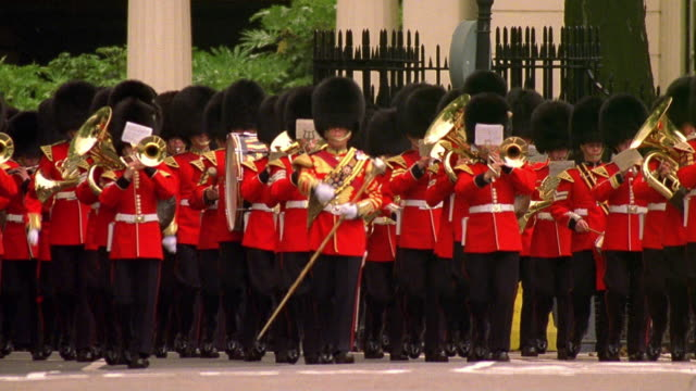 Wide shot the Queen's royal guard playing instruments and marching in front of Buckingham Palace / London