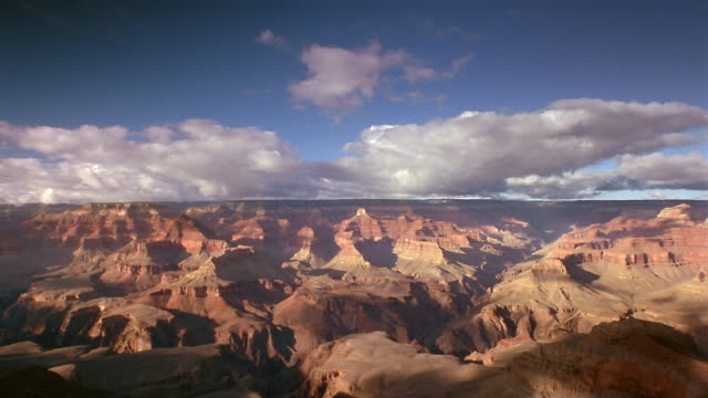 Wide shot thick clouds in blue sky hanging over Grand Canyon / Arizona
