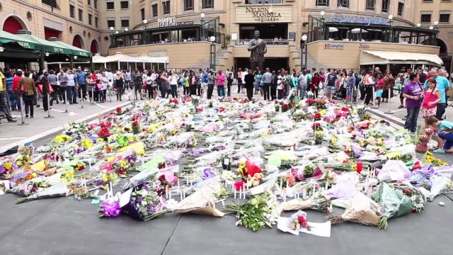 wide shot thousands of mourners leave flowers at nelson mandela square on december 7 2013 in johannesburg south africa mourners have been gathering... - nelson mandela stock videos and b-roll footage