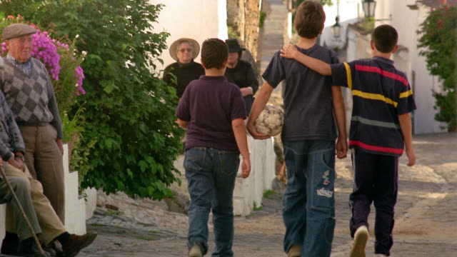 Wide shot three boys walking together on village street / one carrying soccer ball / Monsaraz, Portugal
