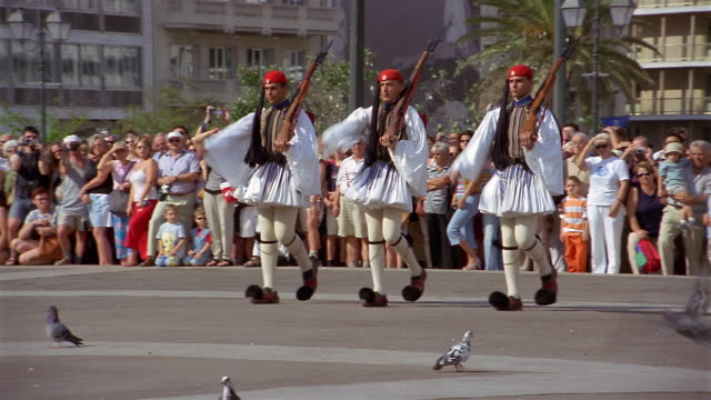 wide shot three evzones (greek presidential guards) marching in parade / athens, greece - griechische flagge stock-videos und b-roll-filmmaterial