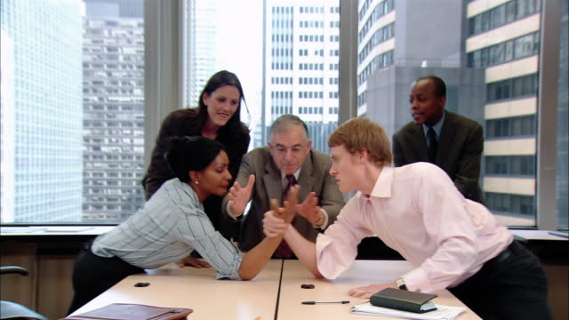 wide shot three men and two women at meeing in board room/ all standing up/ man and woman removing jackets and arm wrestling as three others cheer them on/ woman winning and high fiving other woman/ pan losing man getting up, shamed/ new york, new york - arm wrestling stock videos & royalty-free footage