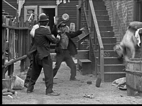 1918 b/w wide shot three men in alley throwing brick at man in window/ man falling out of window/ man and friend picking man up, grabbing his hands and dancing in a circle - oliver hardy stock videos & royalty-free footage