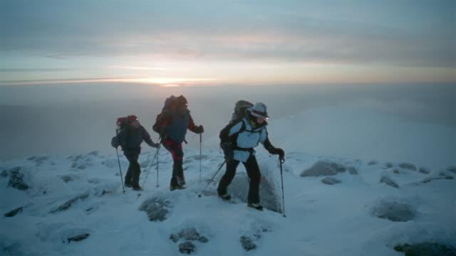 Wide shot three mountain climbers hiking on Mount Washington at sunset / New Hampshire