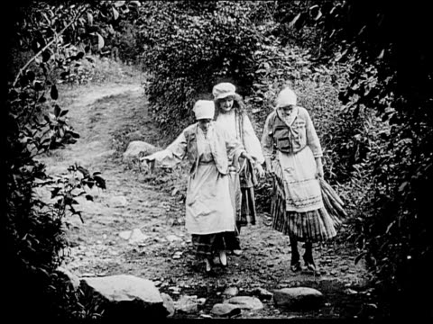 1916 wide shot three peasant woman walking in woods/ stepping across stream/ woman falling - 1916 stock videos & royalty-free footage