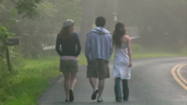 wide shot three people walking on side of country road / man running to catch up to them - maschio con gruppo di femmine video stock e b–roll