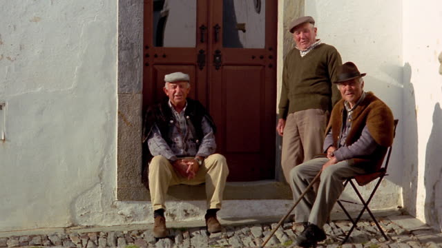 wide shot three senior men talking next to door on side of village street / monsaraz, portugal - traditionally portuguese stock videos & royalty-free footage