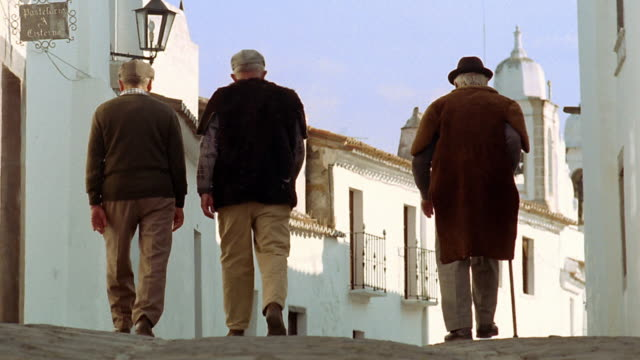 Wide shot three senior men walking away from camera on village street / Monsaraz, Portugal