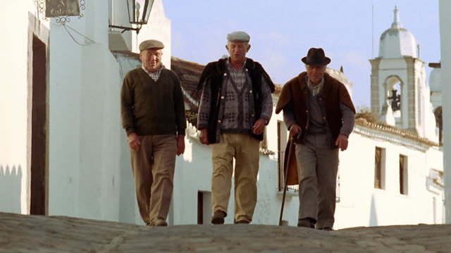 Wide shot three senior men walking toward camera on village street / Monsaraz, Portugal