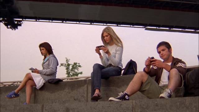 Wide shot three teens sitting under bridge using electronic devices