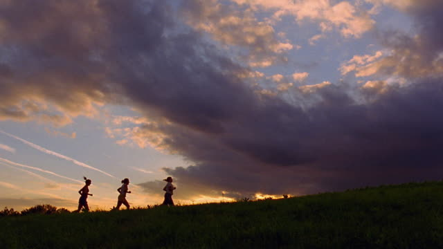 wide shot three women running across field at dusk / vermont - the end stock videos & royalty-free footage
