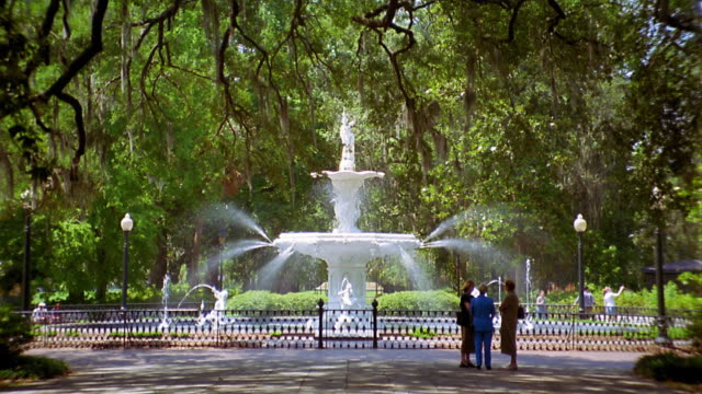 wide shot three women stand next to a fountain in monterey square / savannah, georgia - savannah stock videos and b-roll footage