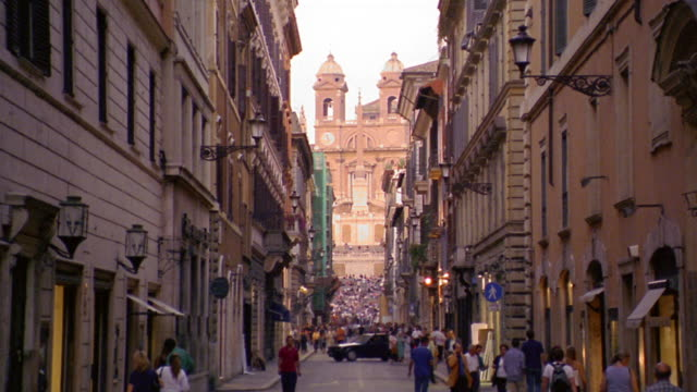 wide shot tilt down busy city street with trinita dei monti church + spanish steps in background / rome, italy - panoramica verso il basso video stock e b–roll
