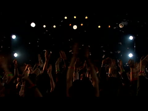 Wide shot tilt down confetti falling from ceiling in nightclub/ tilt down zoom in crowd clapping/ London, England